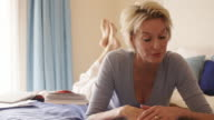 Dolly shot of woman in bedroom lying on bed and reading.