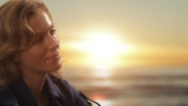 Dolly shot of woman relaxing on beach at sunset/Marbella region, Spain