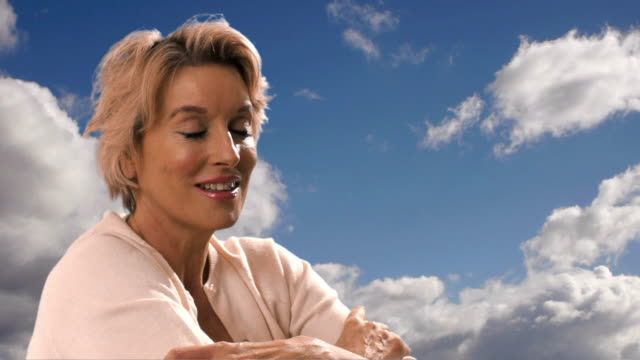 Dolly shot of woman sitting with blue sky and clouds in background.