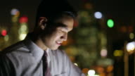 CU Dolly shot of young businessman working on a digital tablet at night.