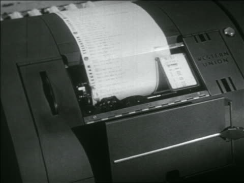 B/W 1956 dolly shot past row of 'teleprinters' with 'Western Union' logos printing on rolls of printer paper