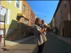 dolly shot PORTRAIT blonde pregnant woman holding baby standing in street surrounded by row houses / NYC