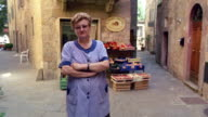 dolly shot PORTRAIT Italian woman standing in front of produce stand in alley / Pienza, Italy