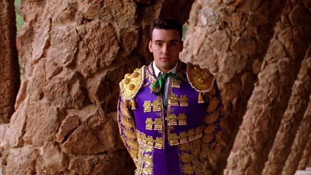 dolly shot PORTRAIT man in matador uniform standing next to slanted columns in Parc Guell / Barcelona