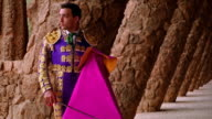 dolly shot PORTRAIT man in matador uniform with cape + sword standing near columns / Parc Guell, Barcelona