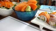 Dolly shot salmon sashimi on black bolw with ice