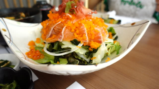 Dolly shot salmon sashimi salad on white bolw