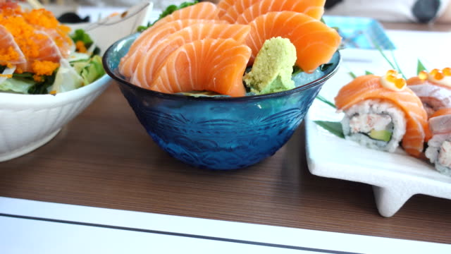 Dolly shot salmon sushi with avokado in white dish