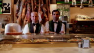 dolly shot SHAKY PORTRAIT two men standing behind counter of restaurant/deli smiling / Barcelona