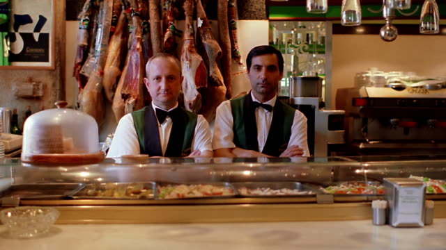 dolly shot SHAKY PORTRAIT two men standing behind counter of restaurant/deli smiling / Barcelona