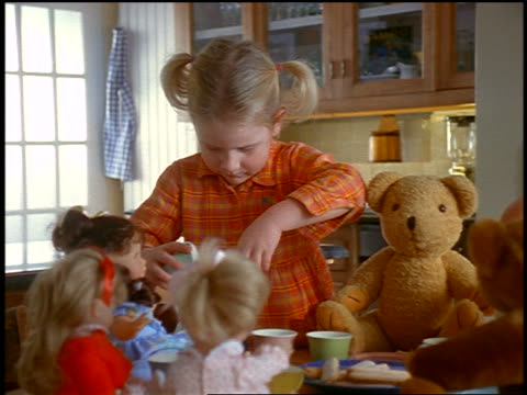 dolly shot PAN small blonde girl playing with tea cup at tea party with dolls + teddy bears
