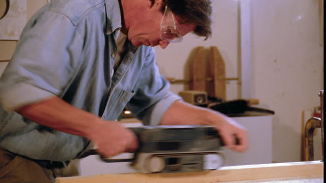 MS dolly shot PAN tilt up man wearing goggles using electric sander on wood in workshop