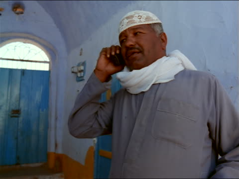 dolly shot to close up middle-aged Nubian man wearing skullcap talking on cell phone in blue hallway / upper Egypt