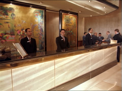 dolly shot to PORTRAIT male hotel desk clerk standing behind front desk in lobby smiling / Egypt