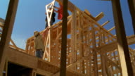 Dolly shot zoom in construction worker handing wooden frame up to other workers on top of house frame / Texas