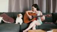 2 Dolly Shots Living with Pet: Smiling woman playing a guitar and man reading a book with their dog in a living room.