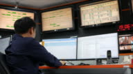 Dolly shot:Youngman working in a control room