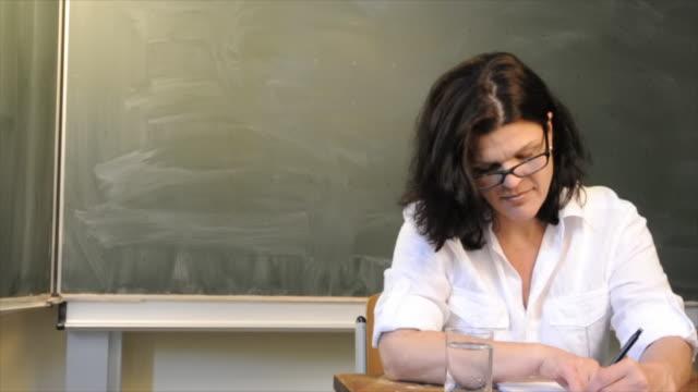 Dolly: teacher correcting exams in classroom
