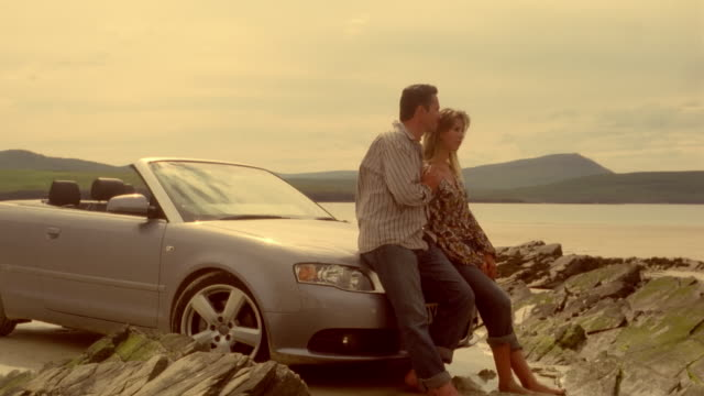 Dolly toward couple leaning against hood of convertible car parked on rocky shore