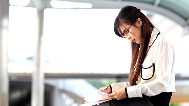 HD DOLLY:businesswoman writing notes on paper.