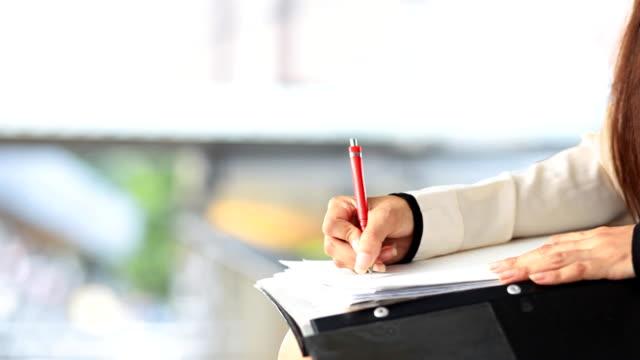 DOLLY HD: mano di donna d'affari scrivendo su carta in un raccoglitore.