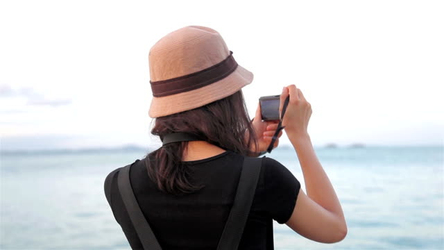 HD Dolly: Frau mit einer digitalen Kamera Fotografieren am Meer.