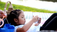 HD dolly:Young girl playing smart phone in the park with family.