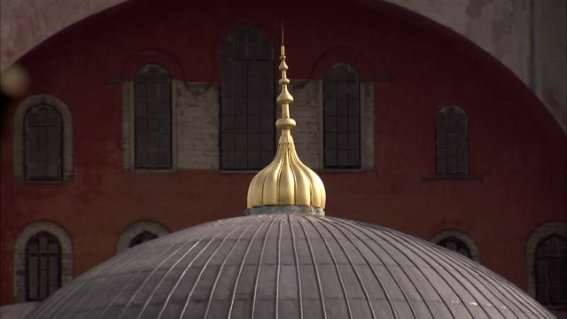 A dome finial fronts a red archway at the Sultan Ahmed Mosque in Istanbul, Turkey. Available in HD