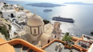 Dome of the local church and the white washed houses of Thira overlooking Cruise ships in  the Aegean Sea on the Island of Santorini, Greece, Europe