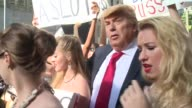 A Donald Trump impersonator appears outside New York's Trump Tower accompanied by two bikini clad models causing a stir in a staged promo event for a...