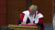 Donald Trump signs a book during a ceremony presenting him with an honorary degree from the Robert Gordon University Scotland