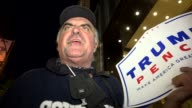 Donald Trump supporter holds proTrump Pence banner sign during AntiTrump rally / Protesters gathered outside of Trump Tower on 5th Avenue and dubbed...