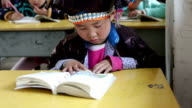 Dong Child in traditional clothing at school reading