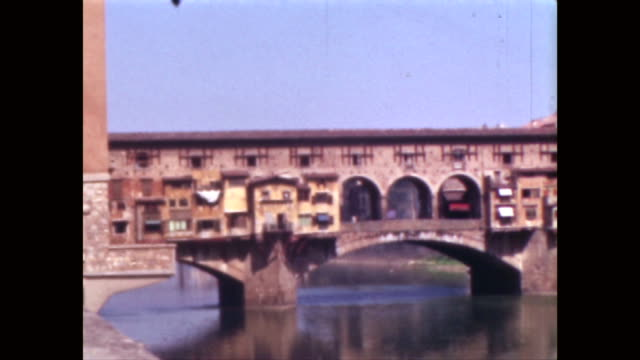 Donkey pulls cart through Piazza Della Signoria bridge over the Arno Ponte Vecchio exterior of the Uffizi high angle view of city including the Duomo