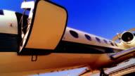 TINTED HIGH CONTRAST door of airplane opening + unfolding /businessmen de-boards + walks down stairs