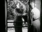 B/W 1946 door-to-door salesman opens screen door and shows vacuum cleaner to the lady of the house