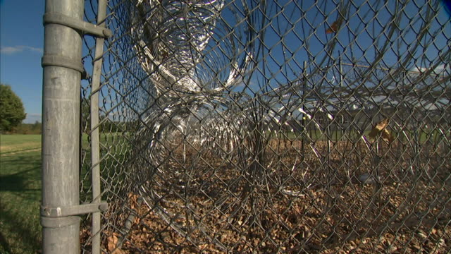 Double coils of razor wire inside chain link prison perimeter fencing RISING UP OUTSIDE FENCING w/ coils on coils razor wire Barrier secure maximum...