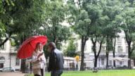 PAN down as couple walks with umbrella, checking text