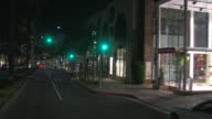Down palm-lined Rodeo Drive at night; driver's POV