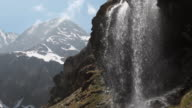 PAN down past waterfall and distant mountains