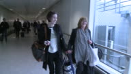 Downton Abbey actresses Michelle Dockery and Phyllis Logan carry a heavy bag between them and hunt for coffee at Heathrow Airport after arriving from...