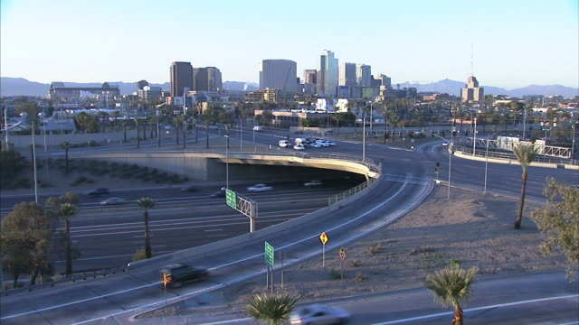 Downtown Phoenix skyline cityscape highrises skyscrapers buildings vehicles trucks moving on highway lower half of frame FG AZ Business District...