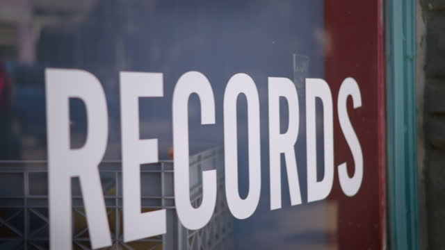 Downtown storefront display window advertises records with decal letters.