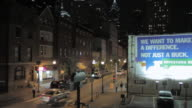 TU Downtown street at night with pedestrian and vehicle traffic, billboard, and city skyline beyond / Philadelphia, Pennsylvania, United States