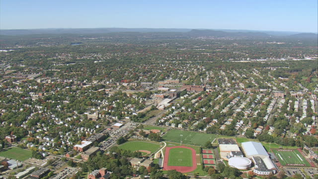 AERIAL Downtown university buildings and residential area amid trees and beside Connecticut River / Springfield, Massachusetts, United States