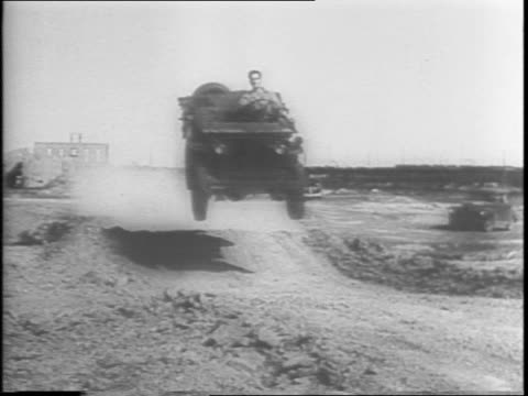 A dozen jeeps on a field Australian soldiers getting ready for jeep tests / individual tests on rough terrain / one flips his jeep over but walks away