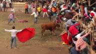 Dozens of men play to be bullfighters inside bullring in an activity called 'toros de pueblo'
