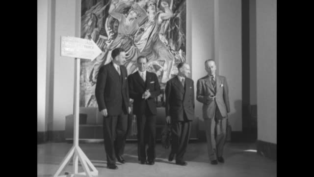 Dr Philip Jessup US ambassador to the UN with others chatting in front of an elaborate art work at the Palais de Chaillot during a session break of...