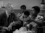 Dr Spock in room talking w/ AfricanAmerican mother w/ baby in cloth diapers standing in lap young boy brother standing BG