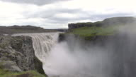 Dramatic cloudy sky over the mighty  Dettifoss  waterfall  in Vatnajökull National Park, Iceland  in summertime